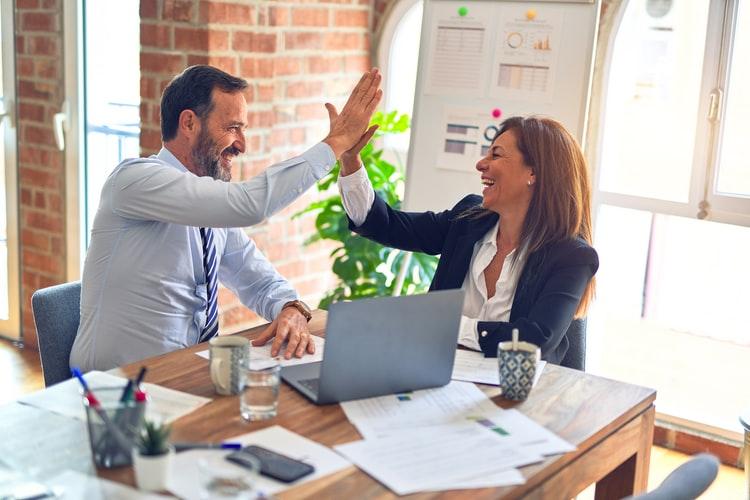 Homem e mulher com papeis e computador em cima da mesa sorriem enquanto se cumprimentam.