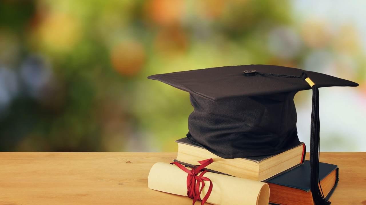 como-conseguir-uma-bolsa-de-estudos - capelo em cima de um livro, acompanhado de um diploma