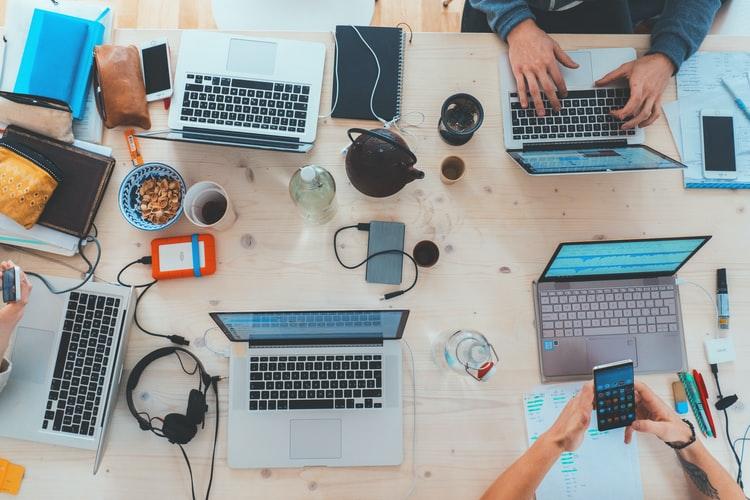 Vários computadores, celulares e materiais de estudo espalhados sobre uma mesa.