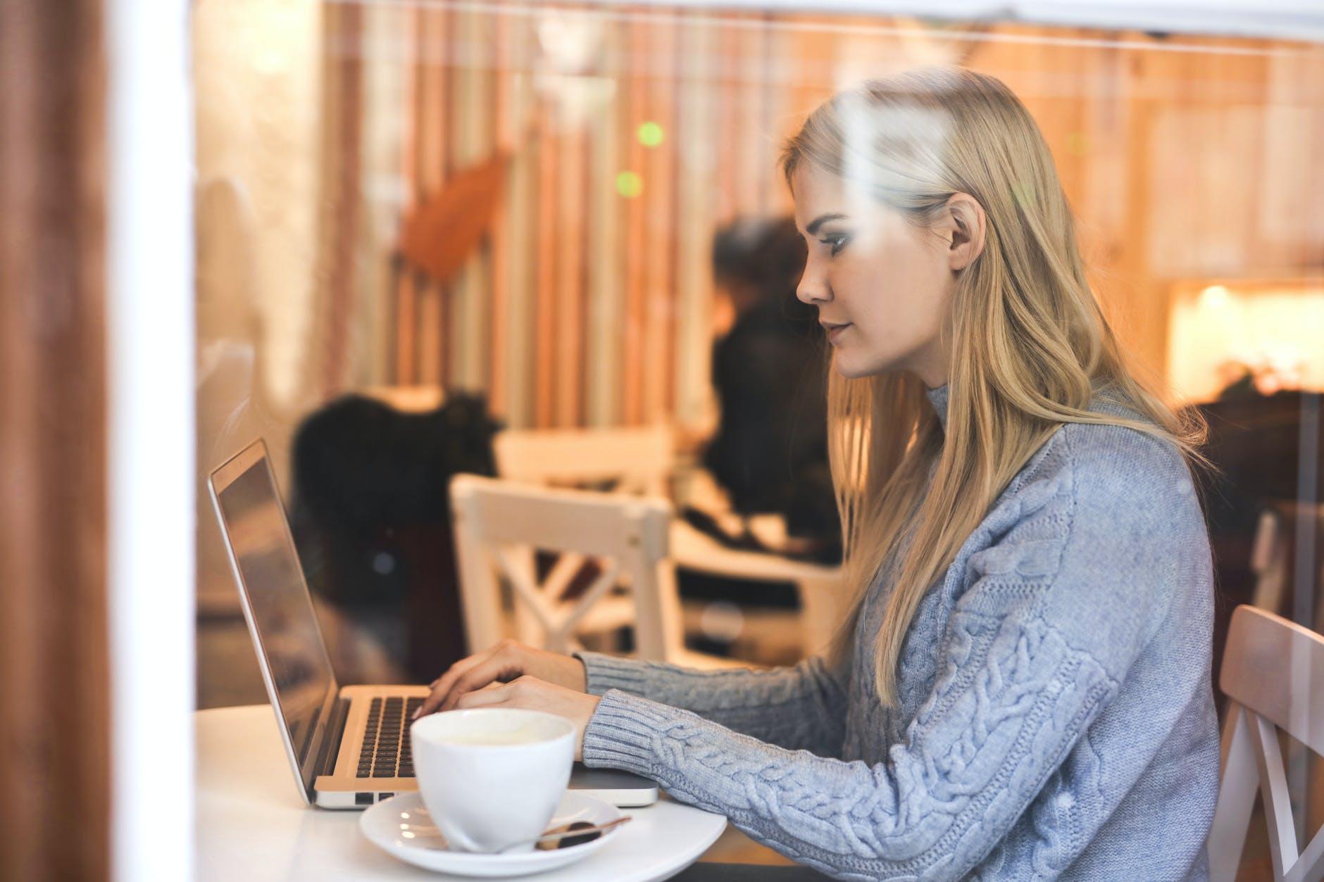 mulher jovem mexendo em notebook em uma cafeteria.