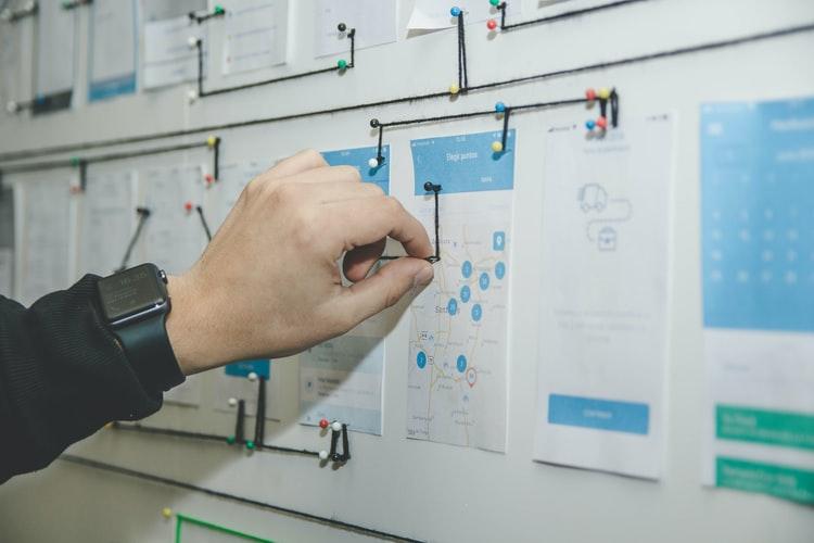 Mão masculina conectando bilhetes em um mural.