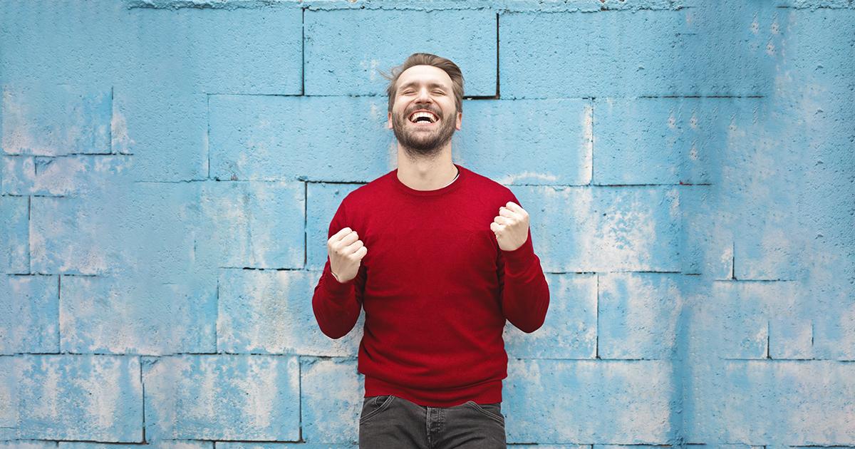 livros-sobre-autocontrole - homem feliz de blusao vermelho em frente a muro azul
