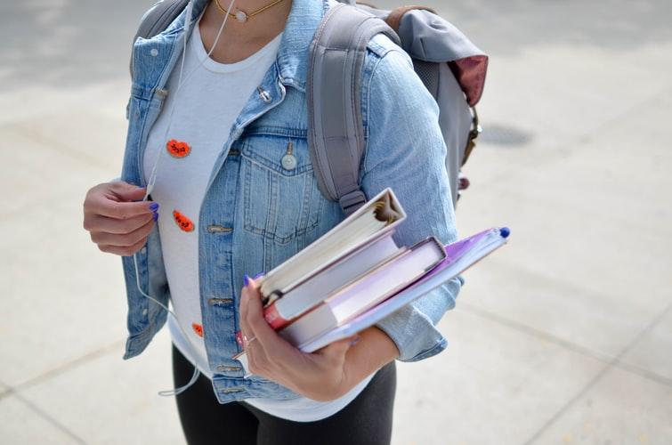 mulher jovem com livros e cadernos em mãos.