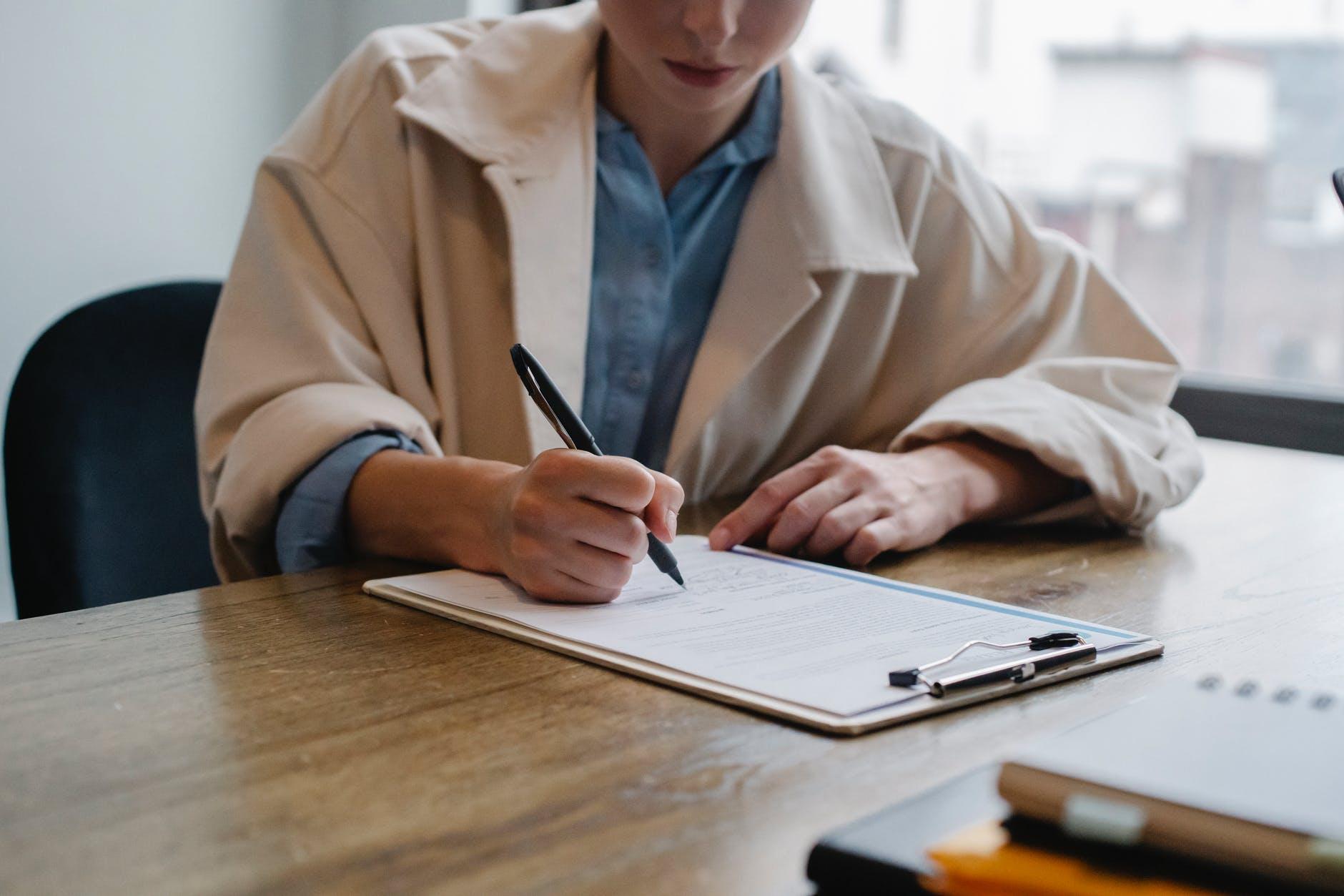 mulher jovem preenchendo documento em planilha.