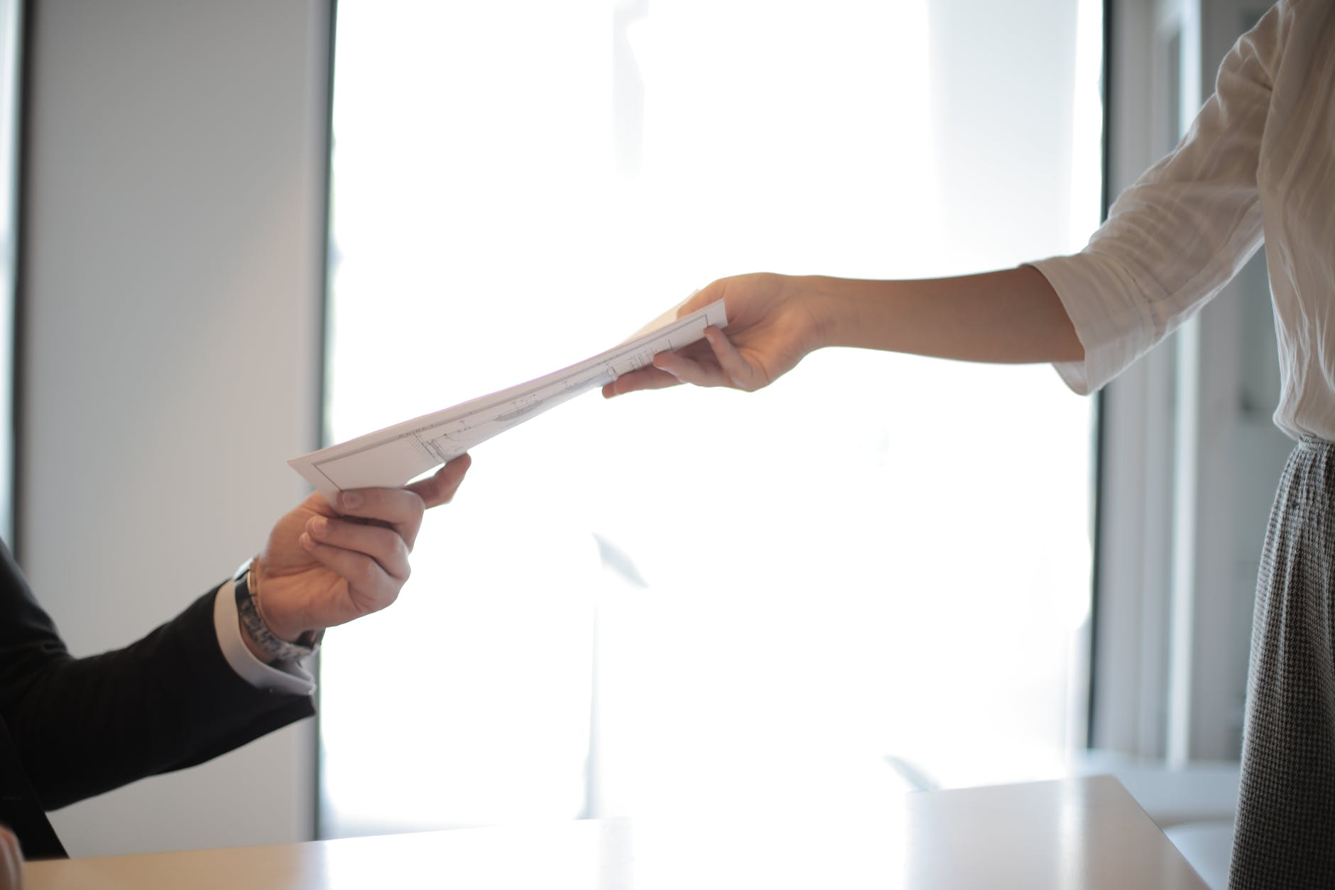 pessoa entregando um documento em mãos para outra.