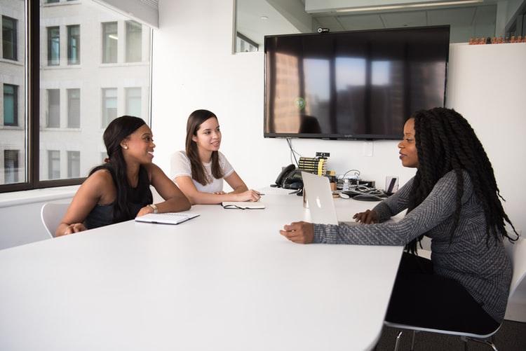 três mulheres conversando em uma mesa. Elas estão em ambiente de trabalho.