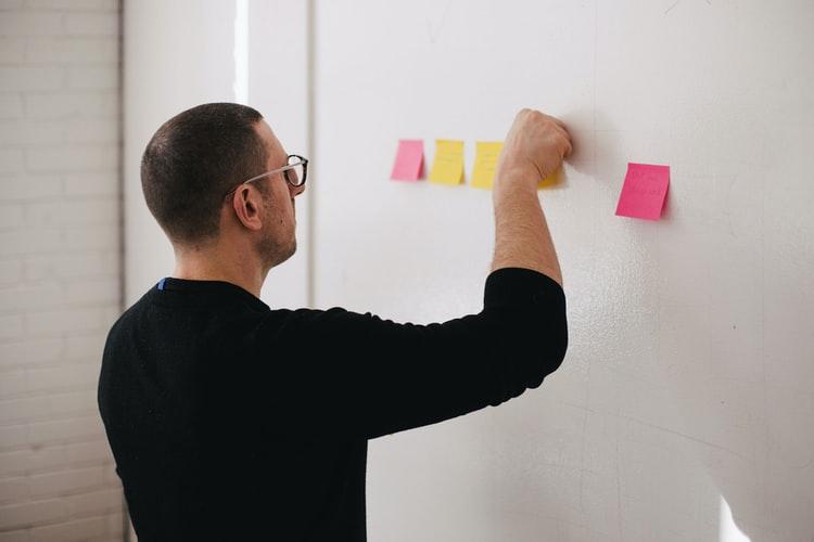 Homem colando notas adesivas coloridas em uma parede.