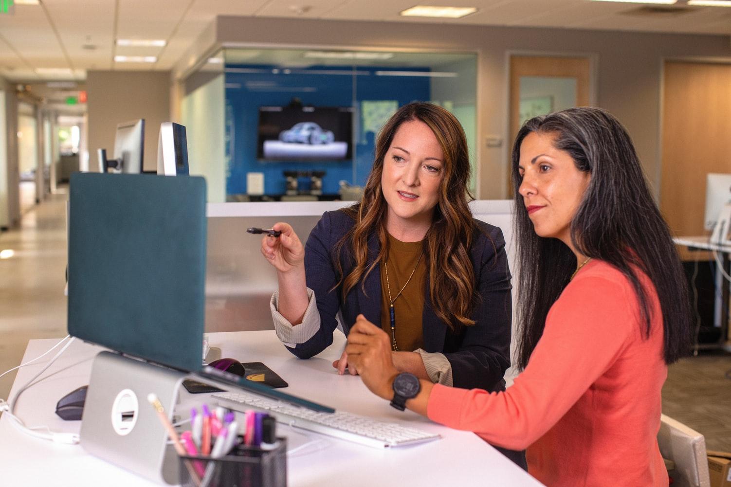 duas mulheres conversando em frente a um computador.