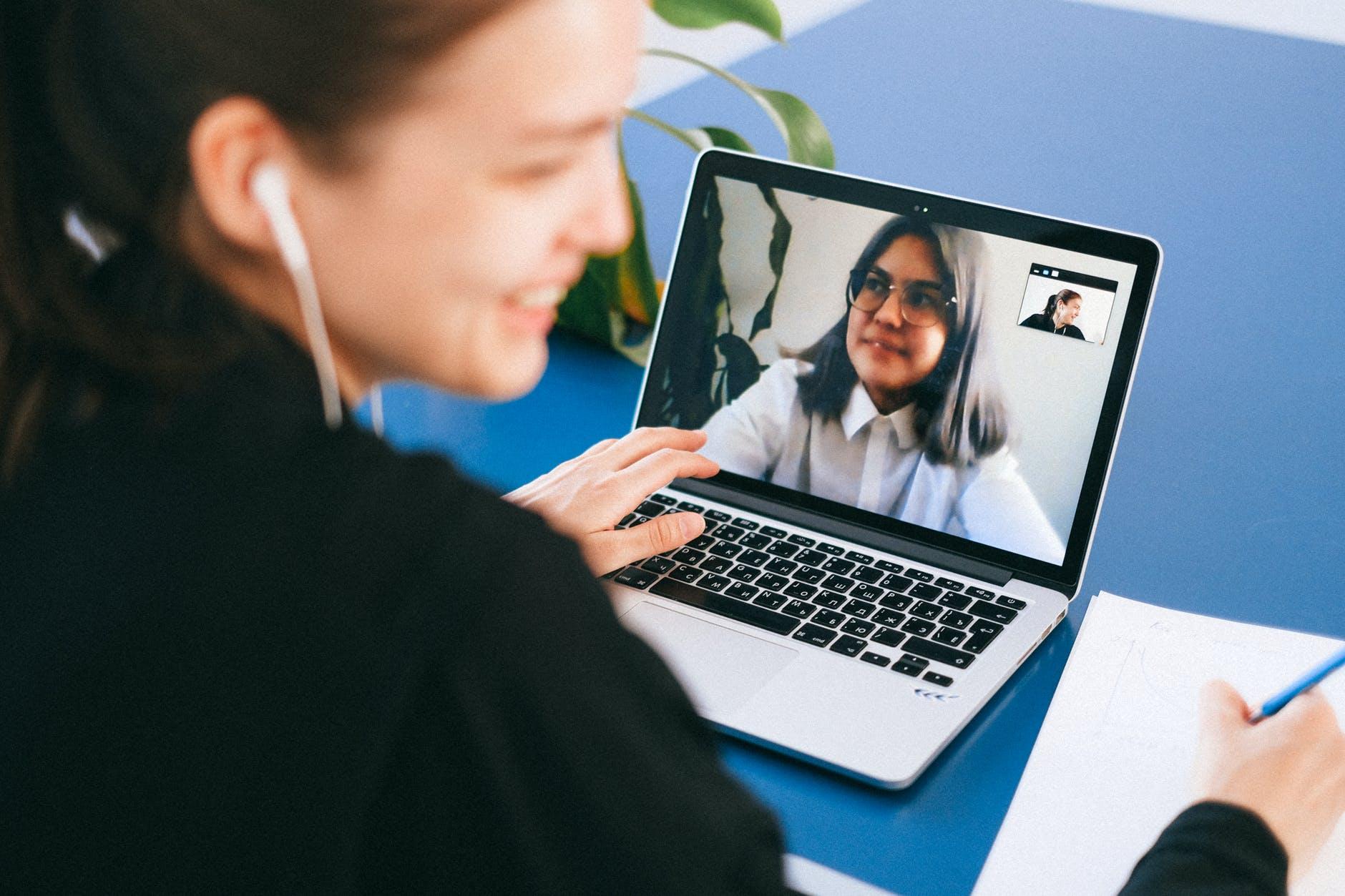 Mulher jovem sorrindo enquanto conversa com outra menina no computador.