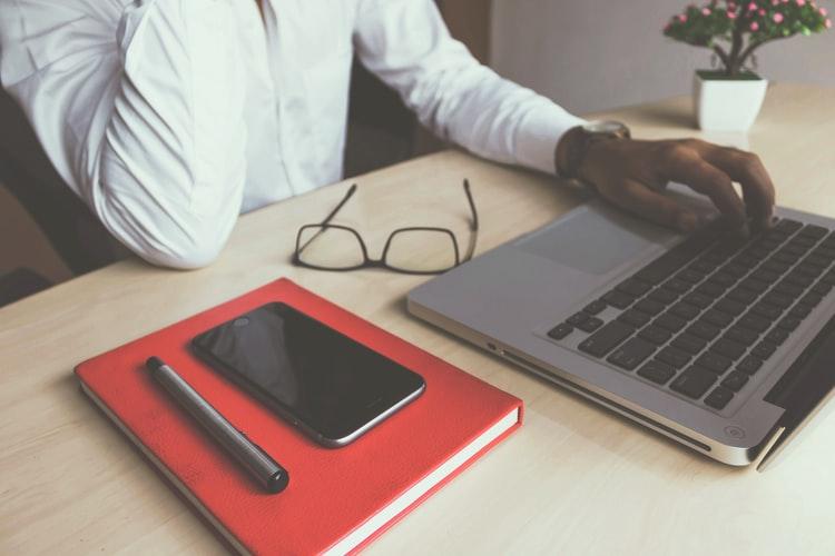 homem com roupa social e, ao lado, notebook, caneta, óculos e celular